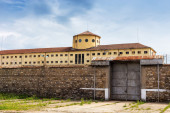 Large prison area with a tall watchtower surrounded with fence a — Stock Photo