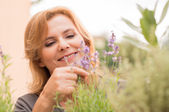 Mature Woman Looking At Flowers — Stock Photo