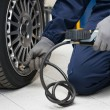 Mechanic Checking Tyre Pressure With Gauge — Stock Photo #57385273