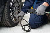 Mechanic Checking Tyre Pressure With Gauge — Stock Photo