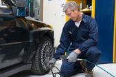 Mechanic Checking Tyre Pressure — Stock Photo