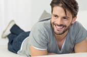 Happy man lying on couch — Stock Photo