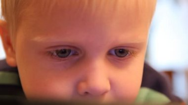 A boy plays in the Tablet PC. Home furnishings, artificial lighting — Stock Video