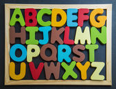 Colorful wooden alphabet on black board — Zdjęcie stockowe