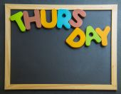 Colorful wooden word Thursday on black board — Stok fotoğraf