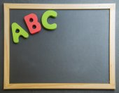 Colorful wooden alphabet ABC on black board — Stock Photo