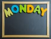 Colorful wooden word Monday on black board — Zdjęcie stockowe
