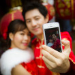 Lovely couple selfie photo by smartphone with red paper chinese — Stock Photo #54981787