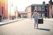 Little kid is holding the suitcase and walking down the sunny st — Stock Photo