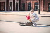 Little kid is opening the suitcase on the sunny street — Stock Photo