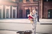 Little kid is holding teddy bear toy on the sunny street — Stock Photo