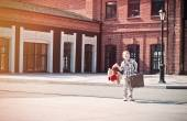Little kid is holding the suitcase and teddy bear toy and walkin — Stock Photo