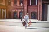 Little kid with suitcase and teddy bear toy crossing the sunny s — Stock Photo