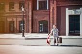 Little kid is holding the suitcase and teddy bear toy crossing t — Stock Photo