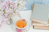 Bunch of lilac, books and teacup — Stock Photo
