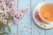 Summer blooming bouquet and a cup of black tea — Stock Photo