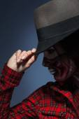 Profile portrait of woman in halloween art on face and hat — Stock Photo