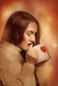 Prachtige jonge vrouw drinken thee uit de beker — Stockfoto