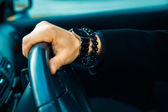 High contrast picture of male hand with watch and bracelet in ca — Stock Photo