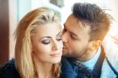 Fashion portrait of couple in love. Man kissing his woman in che — Stock Photo