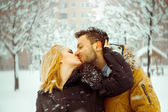 Man and woman happily kissing on the street in the snow — Stock Photo