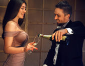 Celebrating a happy laughing couple with a glass of champagne — Stock Photo