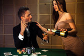 Cute fashionable guy flirting with a lady who pours champagne at — Stock Photo