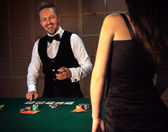 Dealer deals the cards in a casino and laughs — Stock Photo