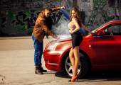 Fashion male model reparing car for voluptuous blonde young woma — Stock Photo