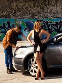 Cara elegante reparando um carro perto da qual fica impressionante menina — Fotografia Stock