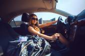 Cutie young girl in sunglasses driving a new car with bag full o — Stock Photo