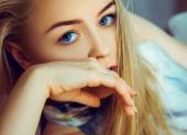 Stunning young blonde woman looking at camera with blue eyes — Stock Photo