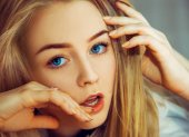 Seductive blonde woman with blue eyes looking at camera — Stock Photo
