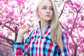 Luxury portrait of serious young blonde girl with flowers — Stock Photo