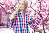 Attractive young blonde with blue eyes looking at camera near bl — Stock Photo