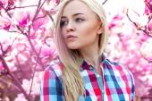 Pretty young blonde girl looking away with pink flowers behind — Stock Photo