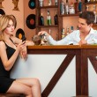 Handsome barman pours a glass of alcohol at the girl as she talk — Stock Photo #74069671