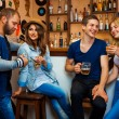 Two loving couples having fun at a bar and drink alcoholic bever — Stock Photo #74070289