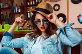 Jonge volwassen vrouw in zonnebril drankje cocktail in bar — Stockfoto