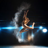 Blonde adult ballerina in jump on stage of theater — Стоковое фото