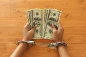 Person with handcuffs holding dollar bills — Stok fotoğraf