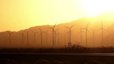 The Sun sets on Wind Turbines generate energy that goes across the mountains to LA — Stock Video
