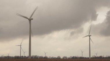 Three Wind Turbines Spin on Farm Land under Developing Storm creating Alternative Energy — Stock Video