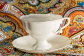 Prcelain cup with saucer in multi colours — Stock Photo