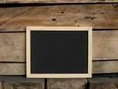 Blackboard on wooden background — Stockfoto