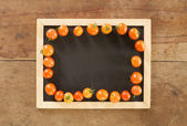 Blackboard and tomato on wooden background — Stock Photo