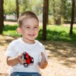 Little child boy plays with toy car — Stock Photo #54546133