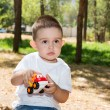 Little child boy plays with toy car — Stock Photo #54546147