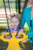 Child girl on swing on playground — Stock Photo