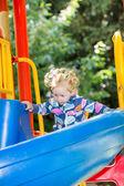 Girl on children's slide on playground — Stock Photo